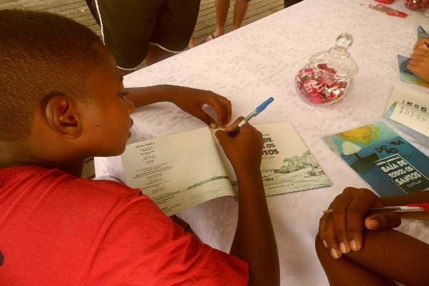 Crianças autografam cartilha ambiental ilustrada por elas, na Bahia Marina